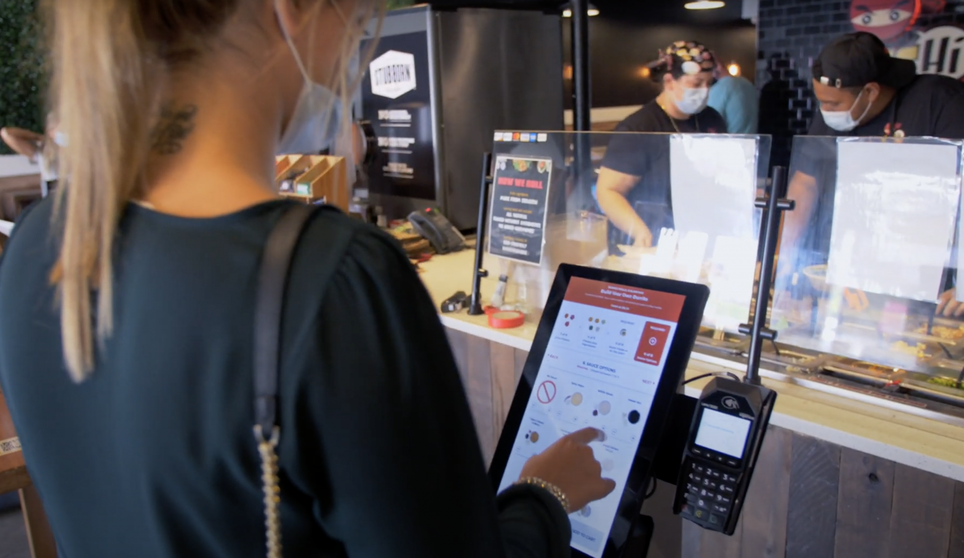 Customer using a self-ordering kiosk in a restaurant